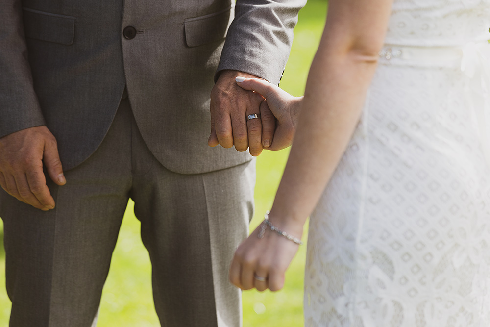 Bride and groom exchanging wedding rings during outdoor wedding